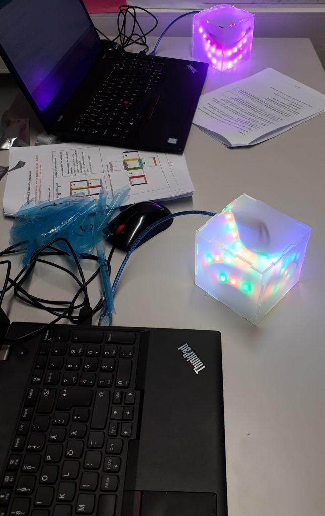 Kaksi tietokonetta ja niihin kytketyt ohjelmoidut ledinauhat monissa väreissä akryylilaatikkojen sisällä
