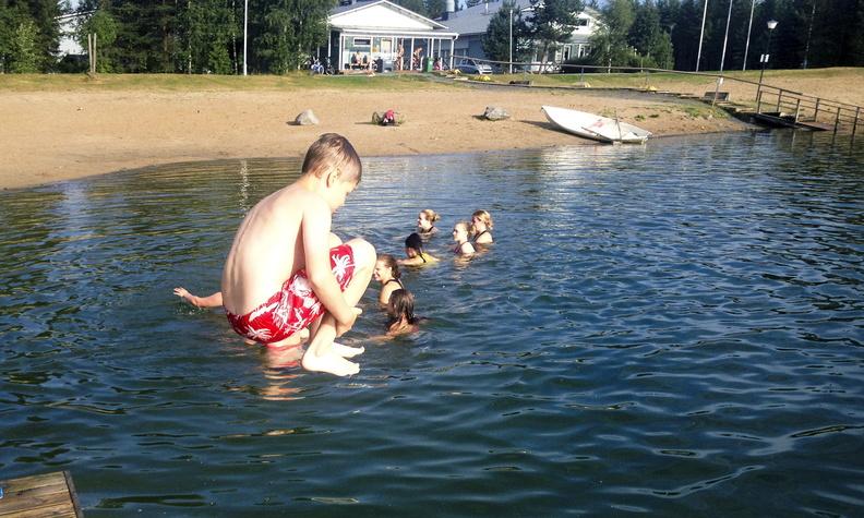 Kuvassa poika hyppää laiturilta lampeen. Taustalla tyttöjä uimassa sekä Tanelinrannan nuorisotalo.
