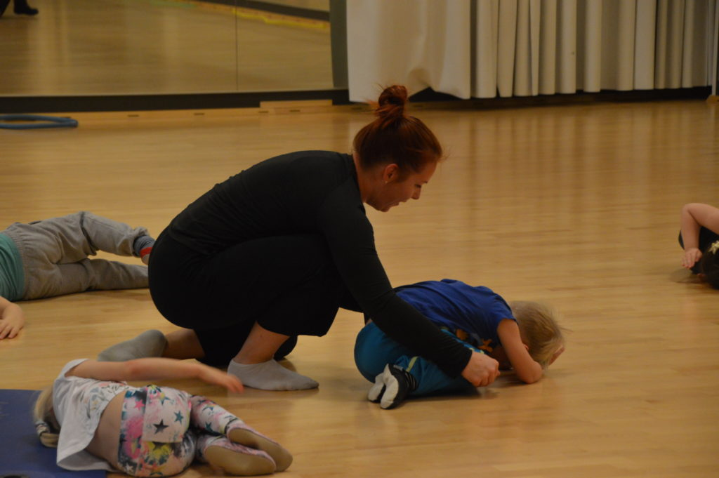 Kuvassa ohjaala neuvoo lasta liikunnassa ryhmän keskellä