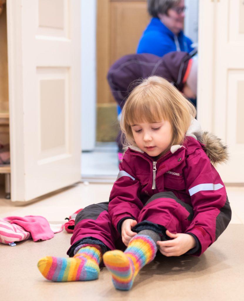 Lapsi pukee värikkäitä villasukkia punainen talvihaalari yllään.
