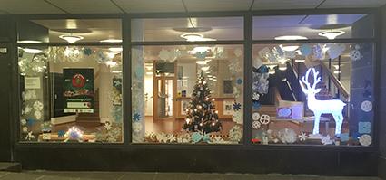 Kaupungintalon ikkuna, jossa lumihiutalekoristeita ja joulukuusi.