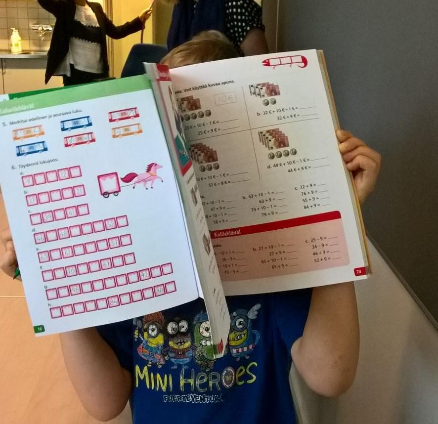 Lapsi pitää avonaista koulukirjaa kasvojensa edessä
