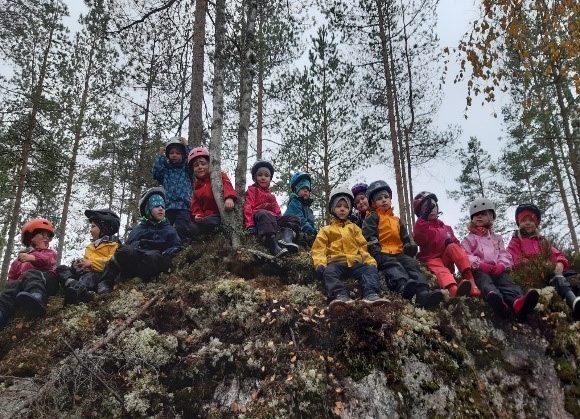 Esikoululaiset istuvat kalliolla syksyisenä päivänä.