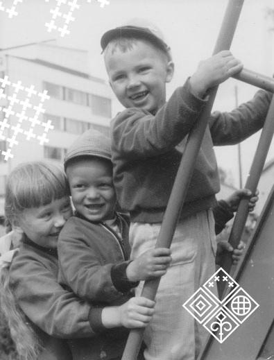 Mustavalkoisessa kuvassa kolme hymyilevää lasta tikapuilla