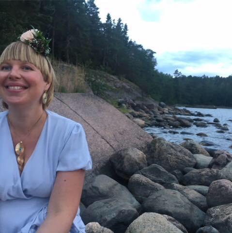 Laura Viitanen istuu kivikossa veden äärellä kesällä.