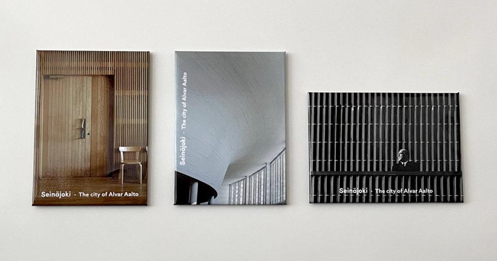 Kolme Aalto-keskusaiheista jääkaappimagneettia: käräjäsalin paneeliseinusta, kirjaston lainaussalin kaareva katto ja kaupungintalon klinkkeri-seinä, jossa arkkitehti Alvar Aalto on parvekkeella.