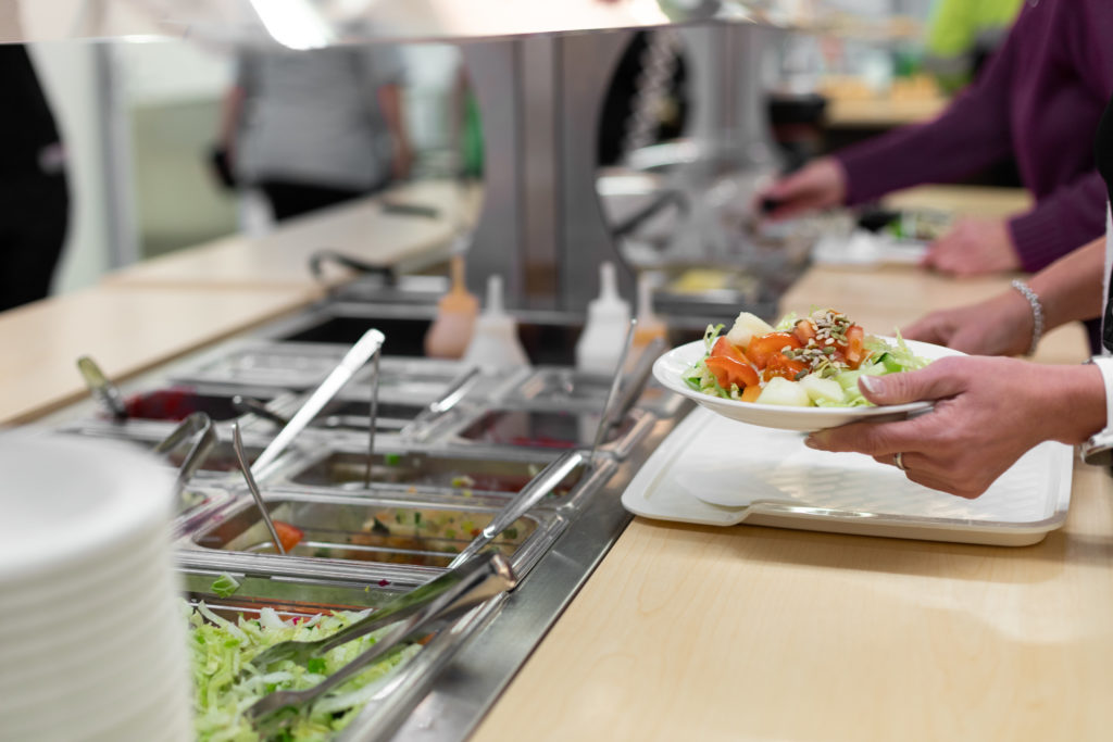 Lounaslinjasto, jossa henkil ottamassa lautaselleen salaatteja ja ruokaa.