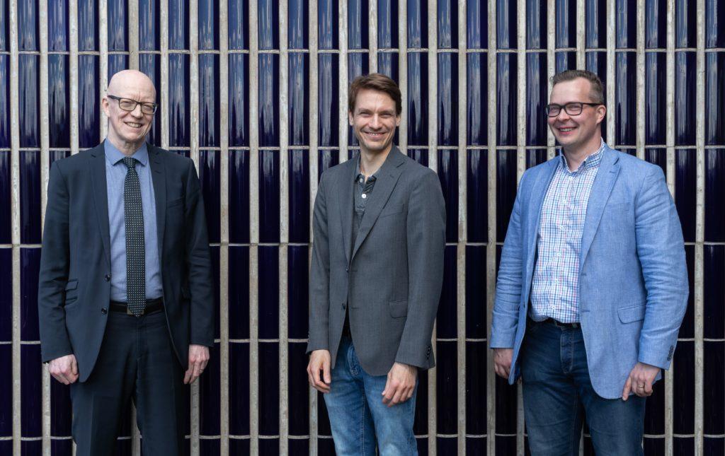Kolme hymyilevää miestä seisoo taustanaan tummansininen sauvakaakeliseinä.