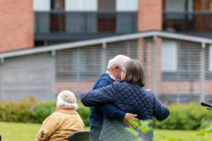 Vanhempi pariskunta tanssii kerrostalon pihamaalla.